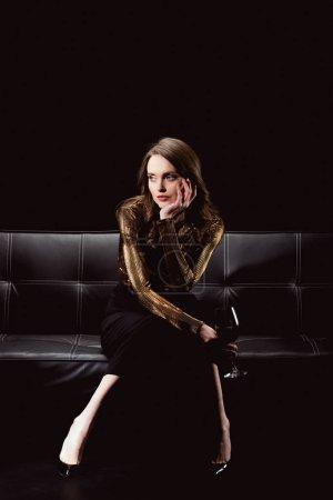 Photo pour Belles femmes glamour assis sur le canapé avec verre de vin rouge et étaiement menton isolée sur fond noir - image libre de droit