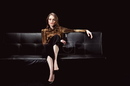 beautiful glamorous woman sitting on couch with glass of red wine isolated on black