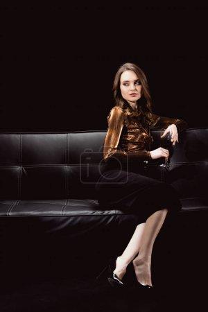 Photo pour Belle femme glamour, assis sur le canapé avec verre de vin rouge et à la recherche de suite isolé sur fond noir - image libre de droit