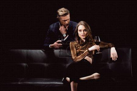 Photo pour Bel homme regardant belle femme avec verre de vin rouge isolé sur fond noir - image libre de droit
