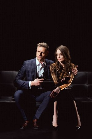 handsome man with glass of red wine sitting on couch and embracing beautiful woman isolated on black