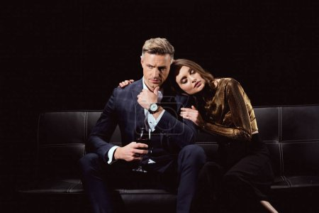 beautiful woman sitting on couch and embracing handsome man with glass of red wine isolated on black