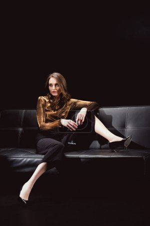 beautiful glamorous woman sitting on couch and posing with glass of red wine isolated on black
