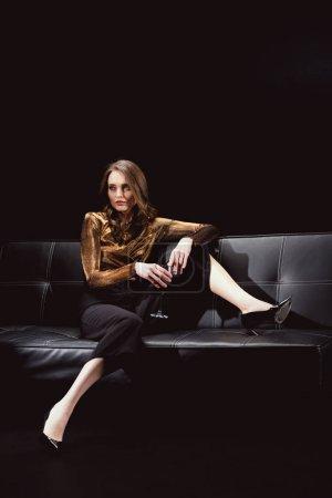 belle femme glamour assis sur le canapé et posant avec un verre de vin rouge isolé sur noir