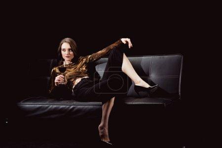 Photo pour Belle femme élégante, couché sur le canapé avec verre de vin rouge isolé sur fond noir - image libre de droit