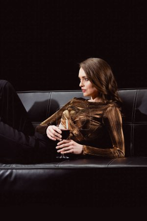 Photo for Beautiful glamorous woman sitting on couch with glass of red wine isolated on black - Royalty Free Image