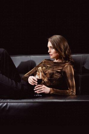 Photo pour Belle femme glamour, assis sur le canapé avec verre de vin rouge isolé sur fond noir - image libre de droit