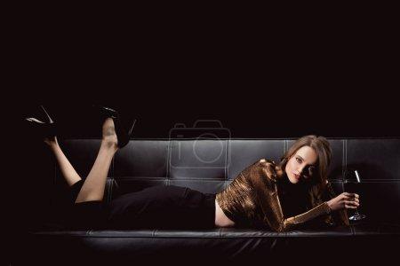 Photo pour Belle femme élégante, couché sur le canapé avec verre de vin rouge tout en regardant la caméra isolée sur fond noir - image libre de droit