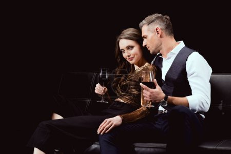 beautiful couple sitting on couch with glasses of red wine isolated on black with copy space