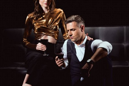 Photo for Cropped view of couple sitting and holding glasses of red wine isolated on black - Royalty Free Image