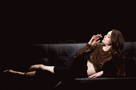 beautiful glamorous woman lying on couch and smoking cigarette isolated on black