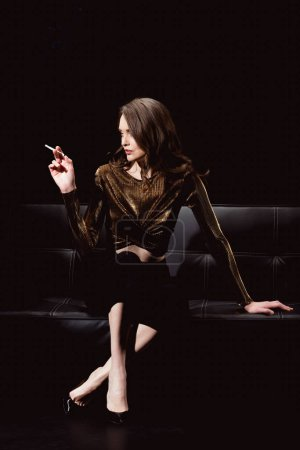 glamorous woman sitting on couch and smoking cigarette isolated on black
