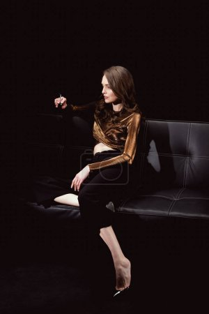 beautiful glamorous woman sitting on couch and smoking cigarette isolated on black