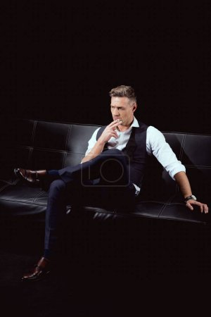 Photo for Serious handsome man in formal wear sitting on couch with cigarette isolated on black - Royalty Free Image