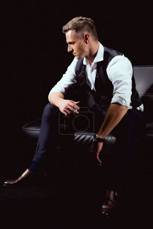 handsome man in formal wear sitting on couch with cigarette isolated on black