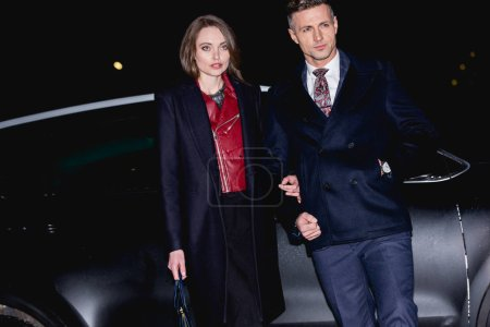 beautiful couple holding hands with car on background