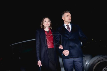 Photo for Couple in formal wear holding hands with car on background - Royalty Free Image