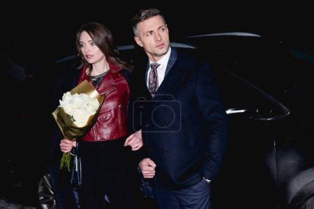 Photo for Beautiful woman with flower bouquet holding hands with man - Royalty Free Image