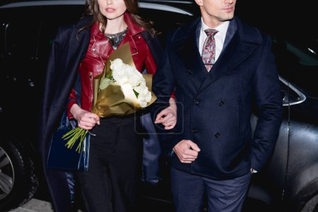 cropped view of woman with flower bouquet holding hands with man