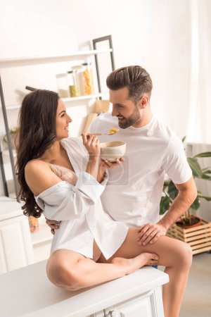 Photo for Smiling woman feeding man with cereal during breakfast in morning - Royalty Free Image