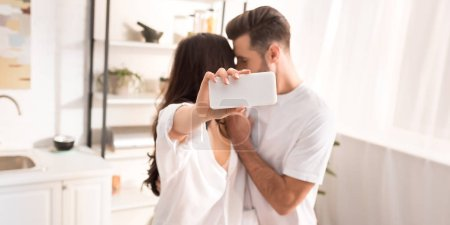 Photo for Couple in white clothes taking selfie on smartphone at home - Royalty Free Image
