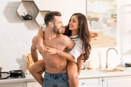 handsome shirtless man giving piggyback ride to smiling woman in kitchen