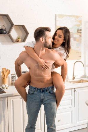 handsome shirtless man giving piggyback ride to smiling woman in kitchen