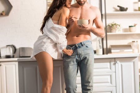 cropped view of young sexy couple during breakfast in morning