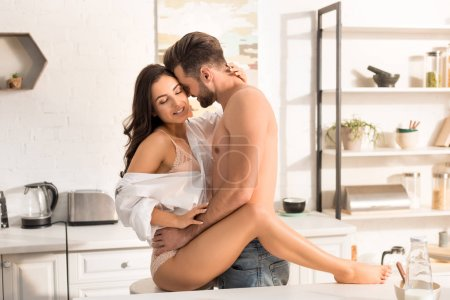 Photo for Young seductive couple hugging in kitchen at home - Royalty Free Image