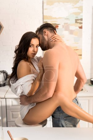 beautiful seductive couple passionately hugging at home