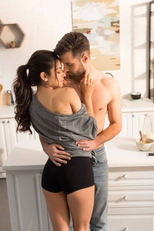 Photo for Selective focus of young seductive couple passionately hugging in kitchen - Royalty Free Image