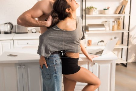 Photo for Cropped view of man pulling hair of woman in kitchen - Royalty Free Image