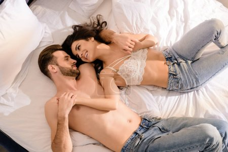 beautiful smiling sexy couple lying in bed and holding hands in morning