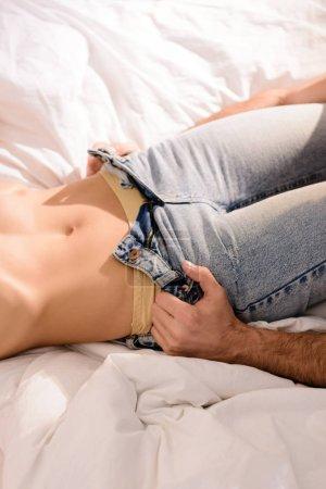 Photo pour Recadrée vue d'homme déshabillé femme sur le lit - image libre de droit
