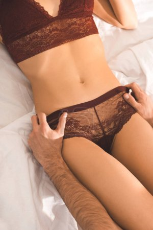 cropped view of man undressing woman in lingerie on bed