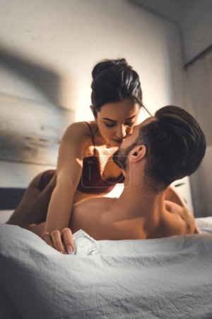 selective focus of young sexy couple lying in bed during foreplay