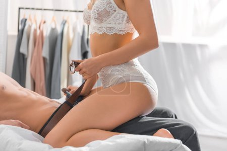 Photo for Cropped view of woman in white lingerie undressing man during foreplay in bedroom - Royalty Free Image