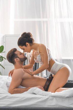 Photo pour Jeune couple séduisant embrassant pendant les préliminaires au lit - image libre de droit