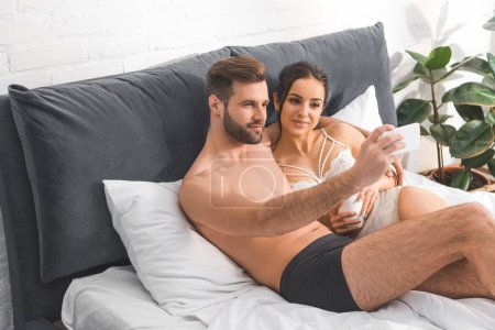 young sexy couple lying in bed and taking selfie on smartphone at home