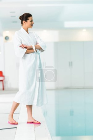 selective focus of woman in bathrobe standing with crossed arms near swimming pool