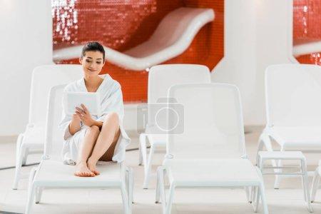 Photo pour Femme attrayante en peignoir couché sur chaise longue et en utilisant une tablette numérique - image libre de droit