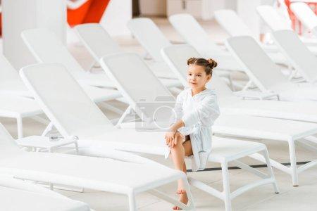Photo pour Mignon enfant en peignoir blanc assis sur la chaise longue - image libre de droit