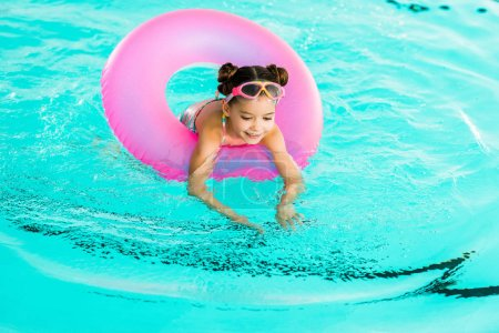 happy child learning swimming with inflatable ring in swimming pool