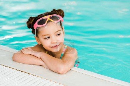 Photo pour Enfant adorable dans googles nager près de bord de la piscine dans une piscine - image libre de droit