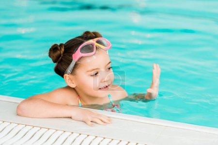 Photo pour Cute kid dans googles nager près de bord de la piscine dans une piscine - image libre de droit