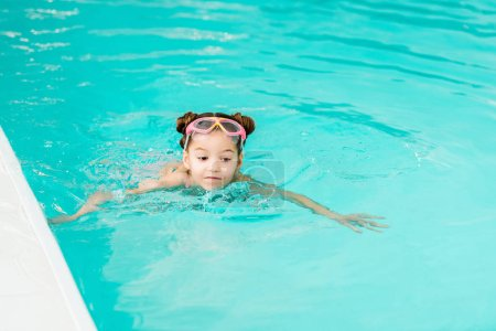 Photo for Cute child in googles learning swimming in blue water in swimming pool - Royalty Free Image