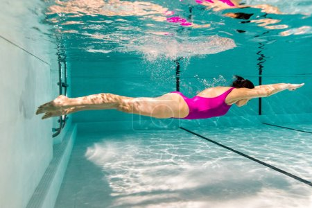 Photo pour Femme plongée sous l'eau en maillot de bain dans la piscine - image libre de droit