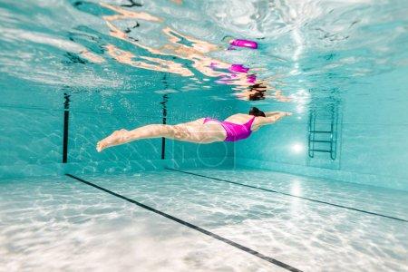 Photo pour Femme plongée sous-marine en maillot de bain dans la piscine - image libre de droit