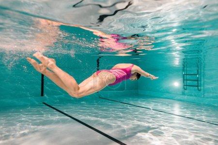 Photo pour Femme plongée sous-marine en maillot de bain rose dans la piscine - image libre de droit