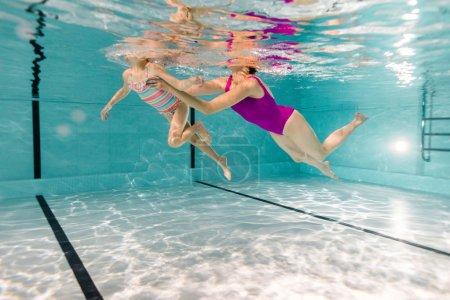 Photo pour Vue recadrée de mère et fille en maillots de bain dans la piscine - image libre de droit